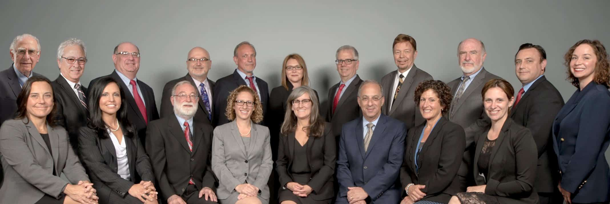 A photograph of the lawyers of Jacobowitz & Gubits, LLP in Walden, NY sitting and standing in two rows